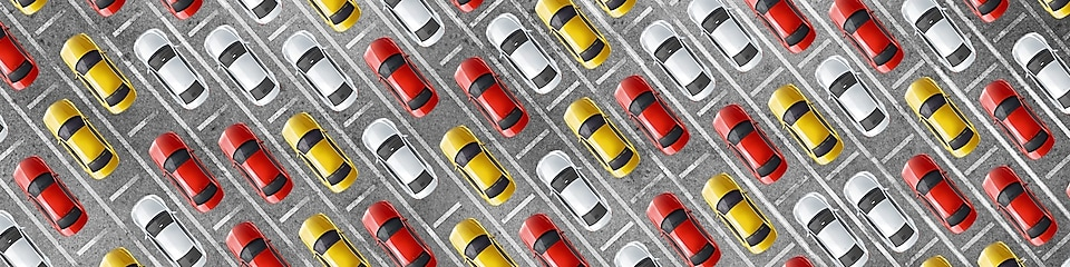 Cluster of red, yellow and white cars