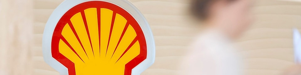 Shell sign with employee climbing steps in the background